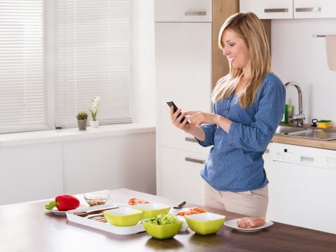 Poland: In the kitchen, smartphone in hand